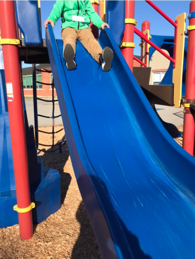student on a slide in a playground