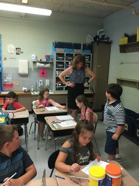 Teacher working with elementary students in a classroom