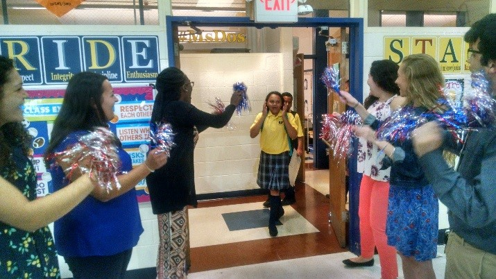 Teachers waving pom-poms at students as they arrive at school