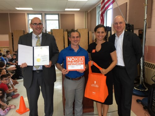 Principal DePalma accepts award and check, with First Gentleman Andy Moffit, Eleni Towns, and Commissioner Wagner