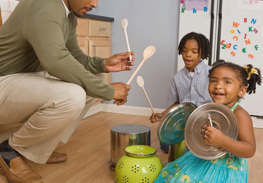 parent with young children making music with kitchen items