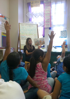 Elementary school students raise their hands during group reading time