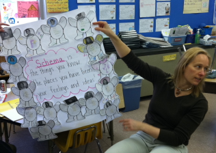 Teacher uses a colorful posterboard to explain concept to her students