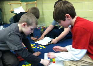 Students using colored tiles to solve math problems