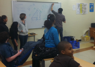 Student solving geometry problem at whiteboard
